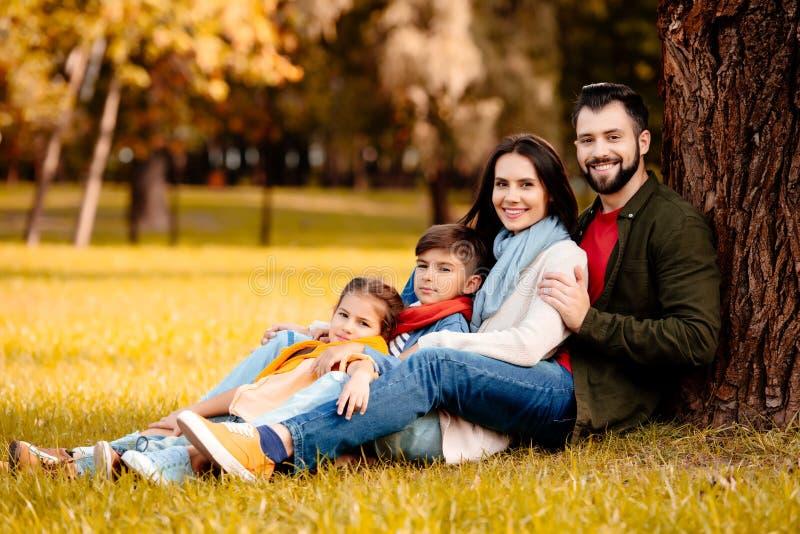 Gelukkige familie met twee kinderen die samen op gras zitten royalty-vrije stock afbeelding
