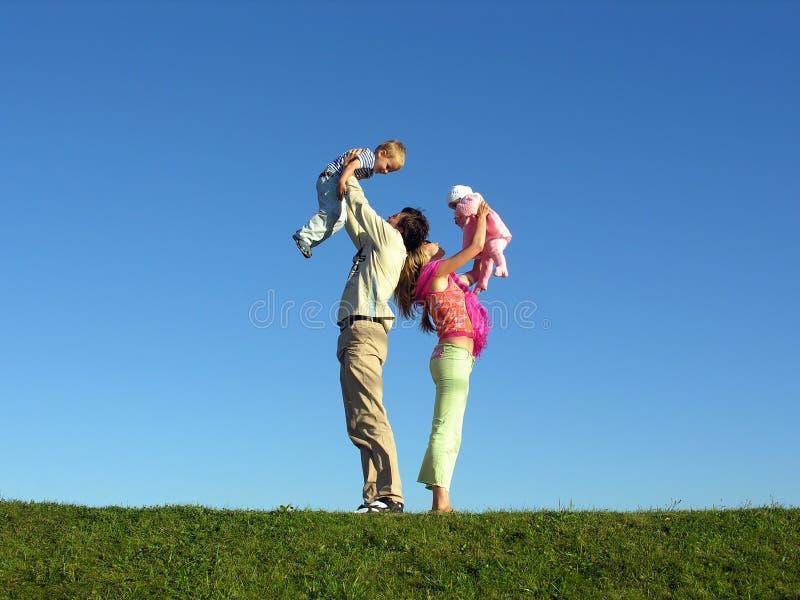Gelukkige familie met twee kinderen op blauwe hemel 2 stock foto