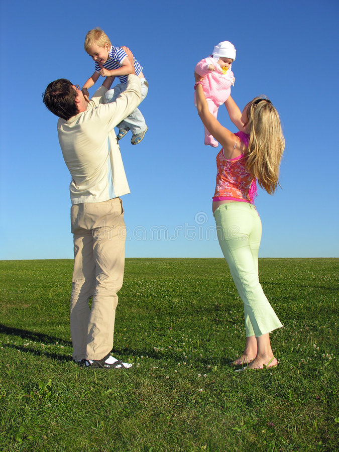 Gelukkige familie met twee kinderen op blauwe hemel royalty-vrije stock foto