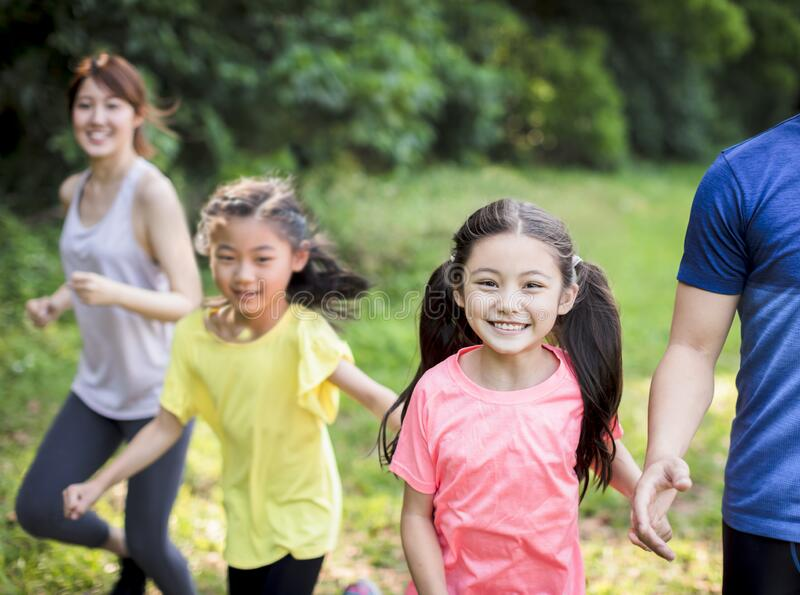 Gelukkige familie met twee meisjes die in het park lopen of joggen royalty-vrije stock afbeelding