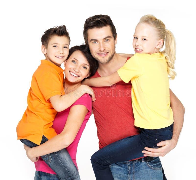 Gelukkige familie met twee schoolkindkinderen stock afbeelding