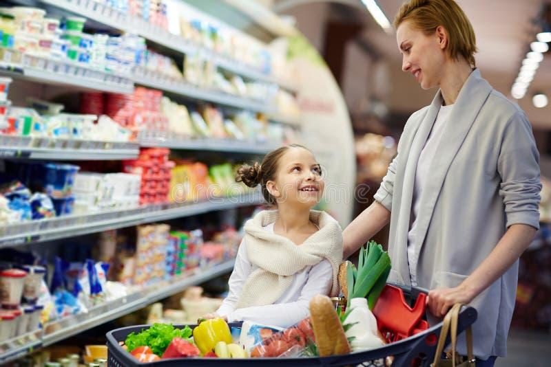 Gelukkige Familie met Volledig Boodschappenwagentje in Supermarkt stock fotografie
