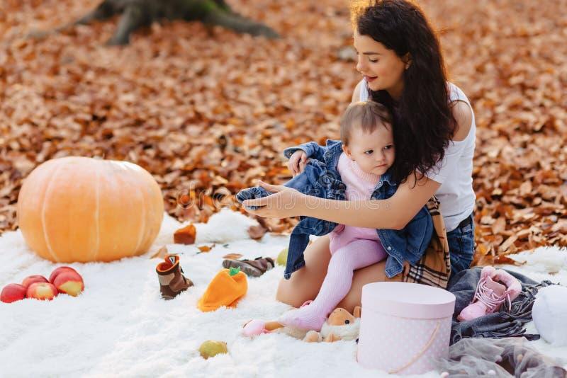 Gelukkige familie met weinig leuk kind in park op geel blad met stock afbeelding