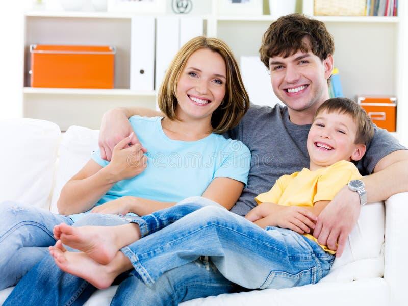 Gelukkige familie met zoon op de bank stock foto