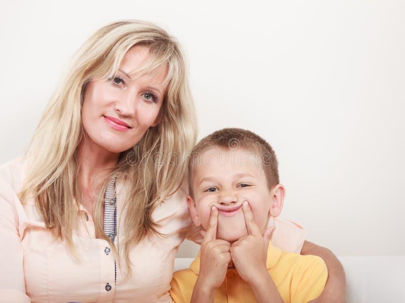 Gelukkige Familie Moeder en jong geitje op bank thuis stock foto