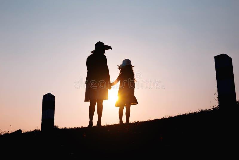 Gelukkige Familie Moeder en zoons het spelen op grasgebieden in openlucht bij avondsilhouet Uitstekende Toon en exemplaarruimte stock foto's