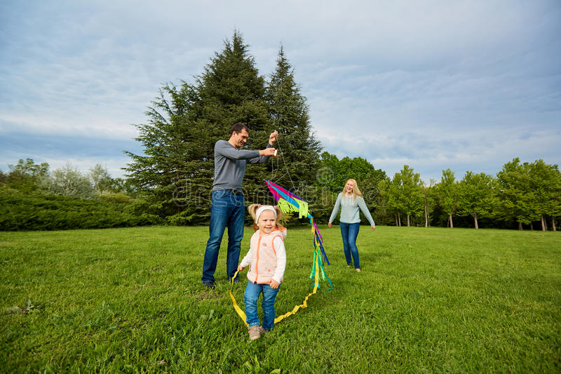 Gelukkige Familie Moeder, vader die, kinderen over een groene weide lopen stock afbeelding