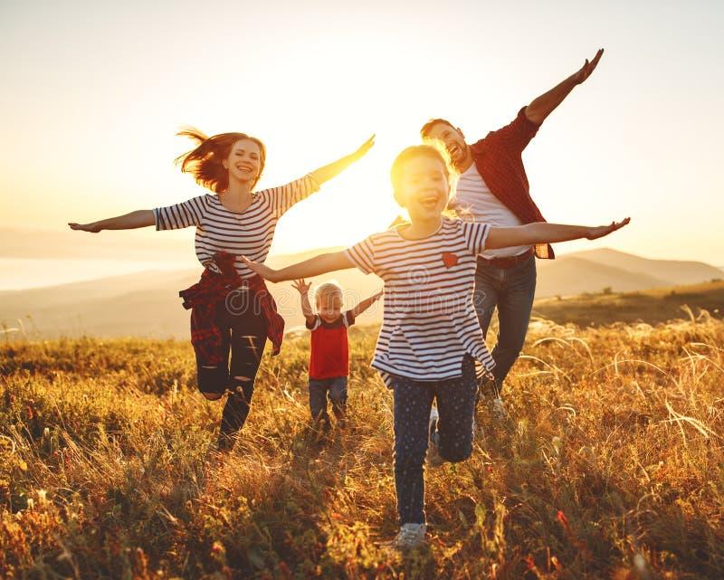 Gelukkige familie: moeder, vader, kinderenzoon en dochter op zonsondergang royalty-vrije stock afbeelding
