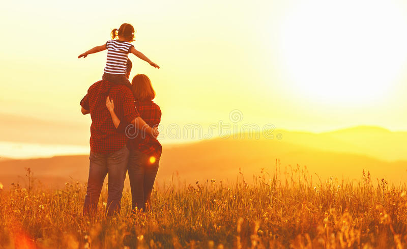 Gelukkige familie: moedervader en kinddochter op zonsondergang stock foto's