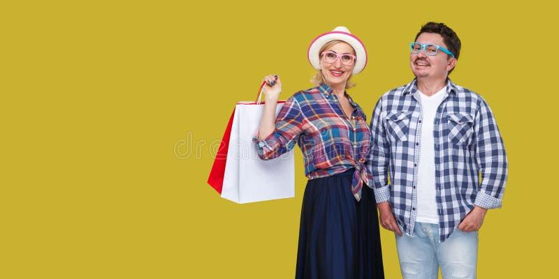 Gelukkige familie na de winkelende, volwassen mens en vrouw in toevallig geruit overhemd die zich en document zak met toothy vere stock foto's