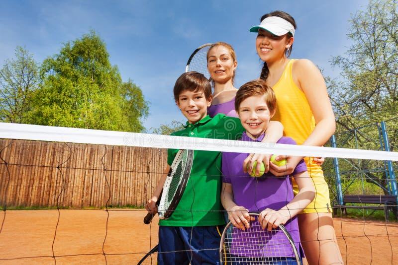 Gelukkige familie na het spelen van tennis in zomer stock afbeeldingen