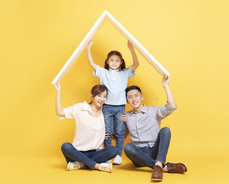 Gelukkige familie in nieuw huis met dakconcept stock afbeeldingen