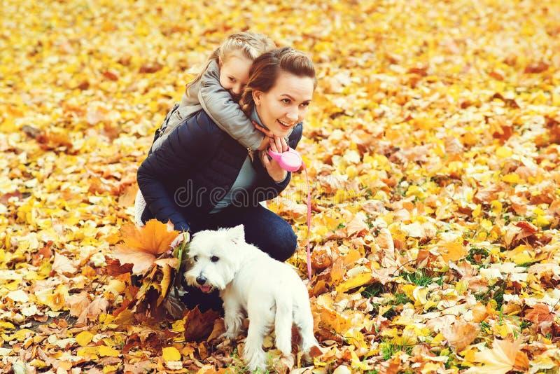 Gelukkige familie op de herfstgang Moeder, dochter en hun hond het spelen in het de herfstpark Familie die van mooie dalingsaard  royalty-vrije stock fotografie