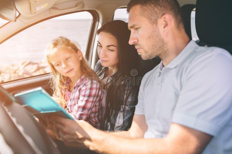 Gelukkige familie op een wegreis in hun auto De papa, het mamma en de dochter reizen door het overzees of de oceaan of de rivier stock foto