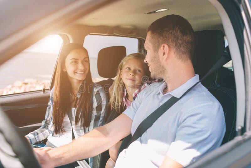 Gelukkige familie op een wegreis in hun auto De papa, het mamma en de dochter reizen door het overzees of de oceaan of de rivier stock fotografie