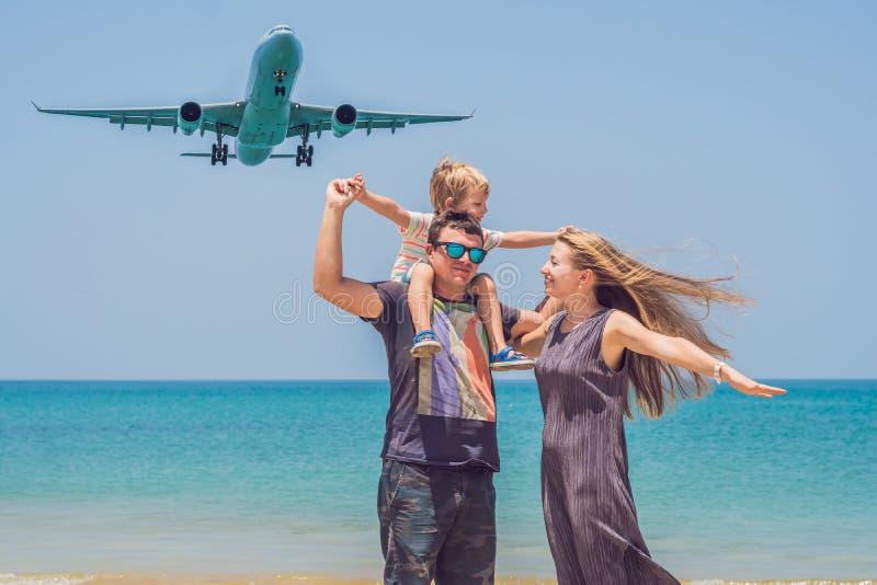 Gelukkige familie op het strand en de landende vliegtuigen Het reizen met c stock foto