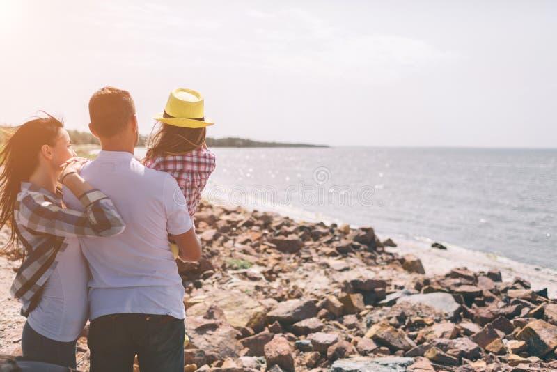 Gelukkige Familie op het Strand Mensen die pret op de zomervakantie hebben Vader, moeder en kind tegen blauwe overzees en hemel royalty-vrije stock afbeelding