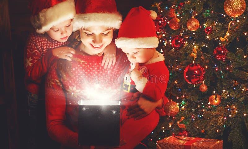 Gelukkige familie op Kerstmisvooravond de moeder en de kinderen ontdekken ma stock afbeelding