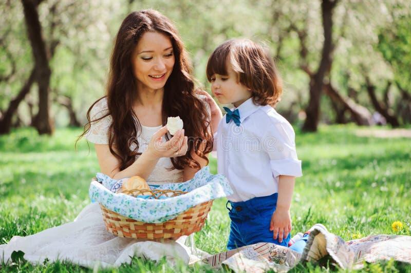 Gelukkige familie op picknick voor moedersdag Mamma en peuterzoon die snoepjes openlucht in de lente of de zomer eten stock fotografie