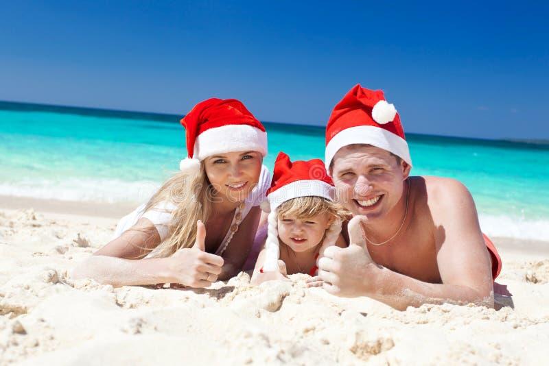 Gelukkige familie op strand in Kerstmanhoeden, vieringskerstmis royalty-vrije stock afbeeldingen