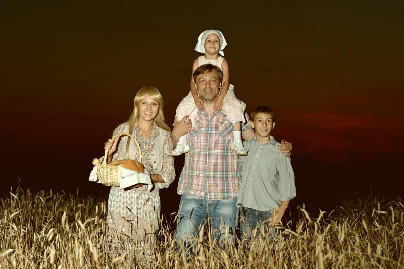 Gelukkige familie op tarwegebied stock foto's