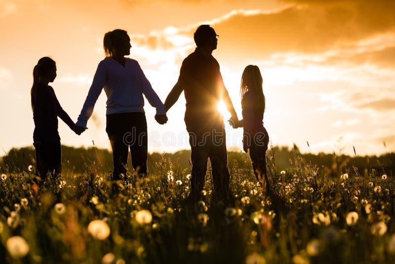 Gelukkige familie op weide bij zonsondergang royalty-vrije stock foto's