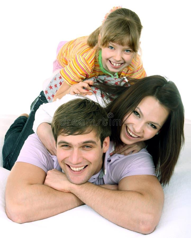 Gelukkige familie op wit bed.