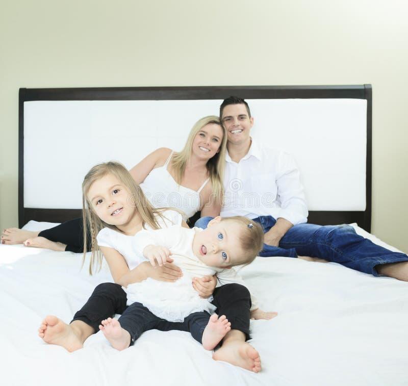 Gelukkige familie op wit bed in de slaapkamer royalty-vrije stock foto's