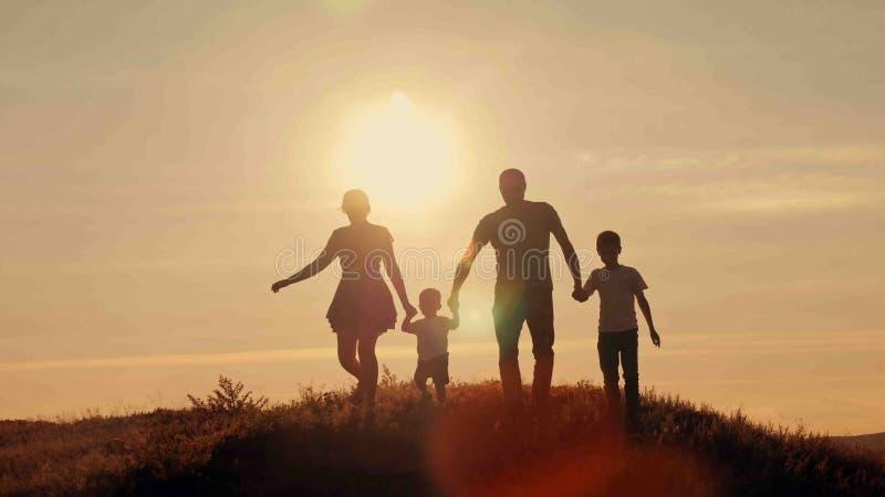 Gelukkige familie op zonsondergangsilhouet stock afbeelding