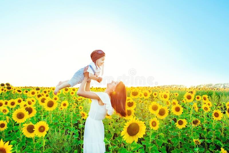 Gelukkige familie in openlucht De moeder werpt baby die omhoog, en op het zonnebloemengebied lachen spelen in de zomer op de aard royalty-vrije stock afbeeldingen