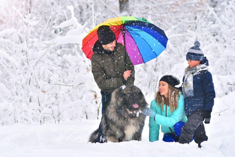 Gelukkige familie in openlucht Familie met huisdierenhond in een de winterbos royalty-vrije stock afbeelding
