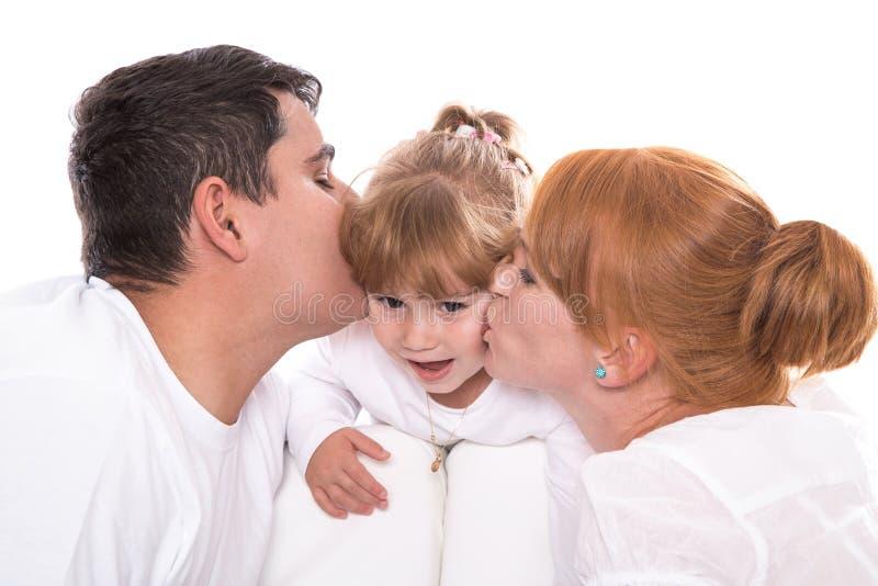 Gelukkige familie: ouders die die dochter kussen op witte backgro wordt geïsoleerd stock foto's