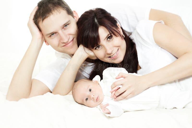 Gelukkige familie: ouders die met pasgeboren baby liggen stock fotografie