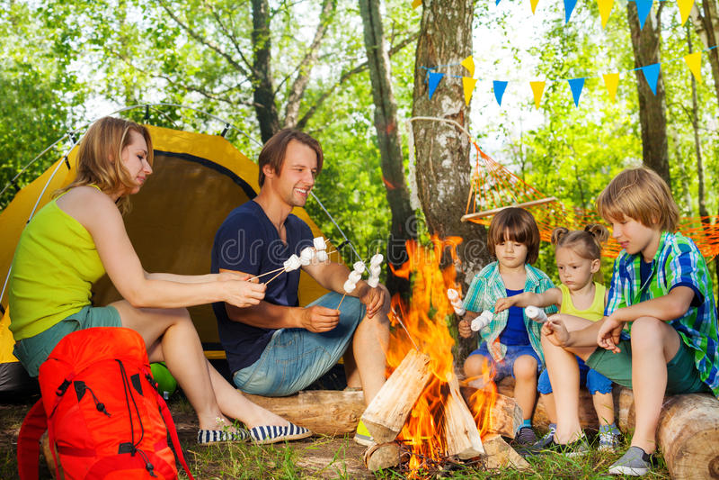 Gelukkige familie roosterende heemst over de brand royalty-vrije stock foto