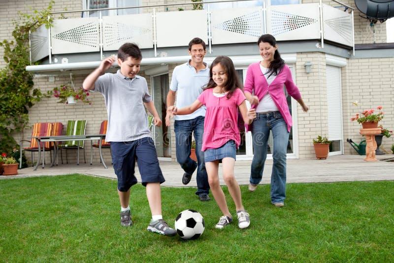 Gelukkige familie speelvoetbal in hun binnenplaats stock foto