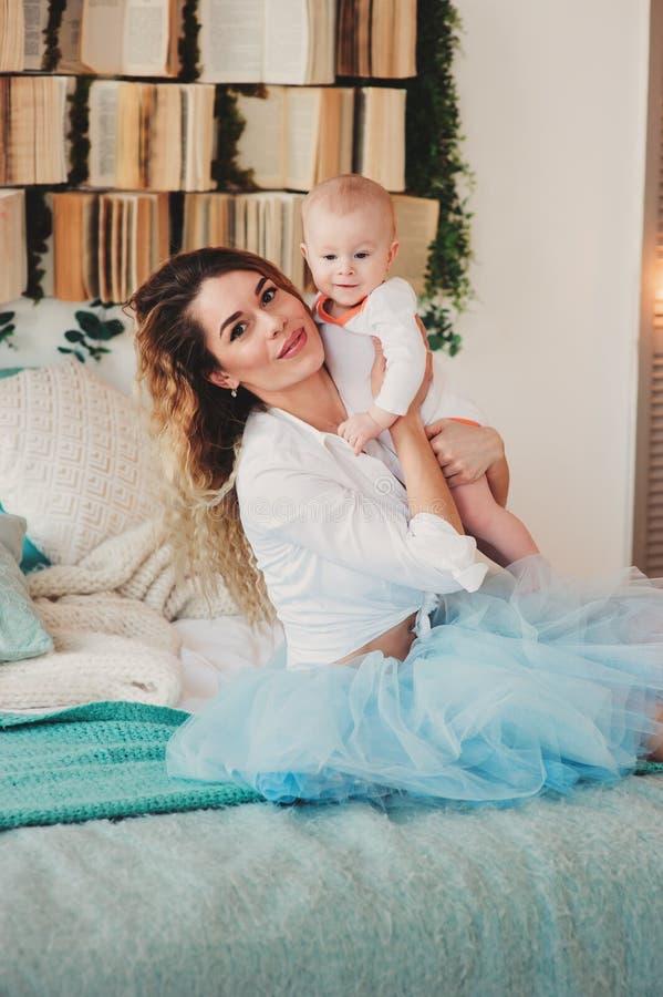 Gelukkige Familie thuis De babyzoon van de moederholding in slaapkamer in comfortabel weekend stock afbeelding