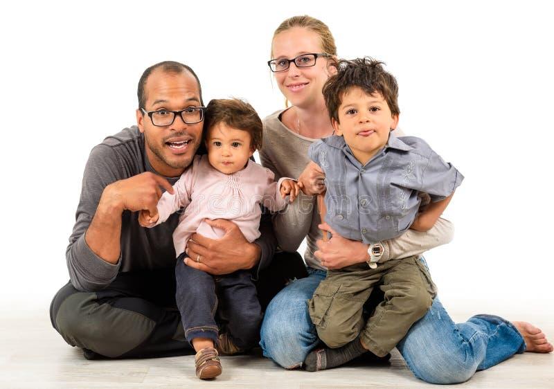 Gelukkige familie tussen verschillende rassen die op wit wordt geïsoleerd stock fotografie