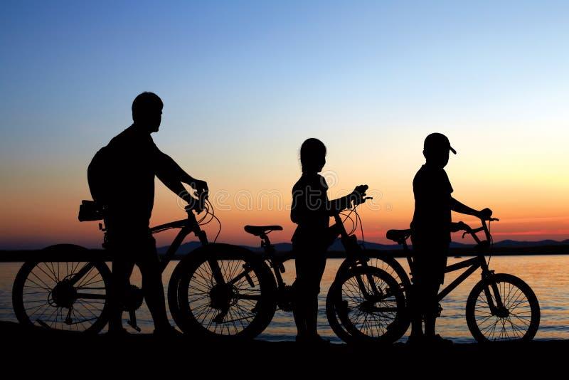 Gelukkige familie - vader met twee jonge geitjes op fietsen met hond stock afbeelding