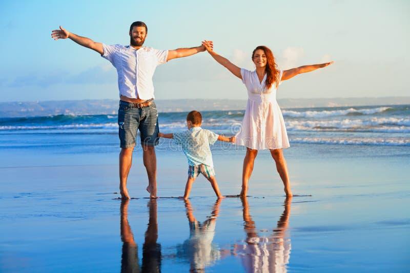 Gelukkige familie - vader, moeder, baby op de vakantie van het de zomerstrand stock foto's