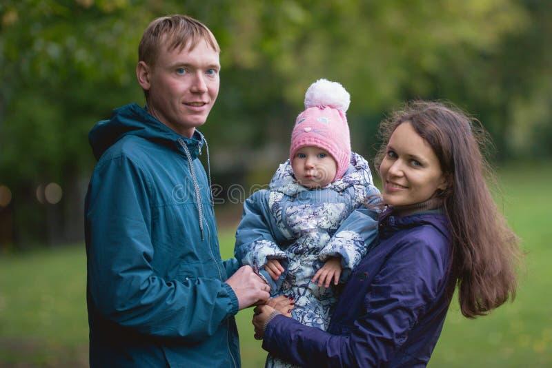 Gelukkige familie: Vader, Moeder en kind - meisje in de herfstpark: de papa, mammababy openlucht stellen, sluit omhoog royalty-vrije stock fotografie