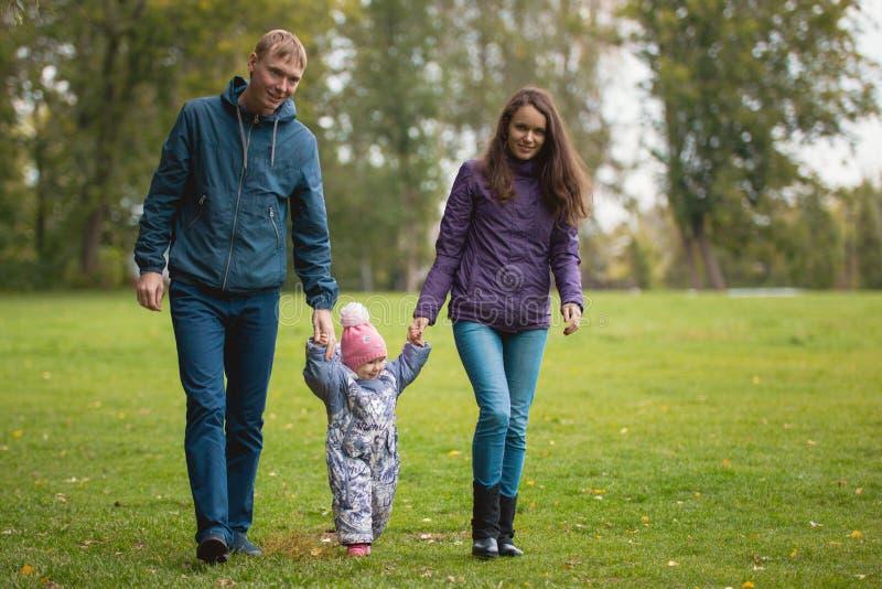 Gelukkige familie: Vader, Moeder en kind - meisje in de herfstpark: lopend bij weide, brede hoek royalty-vrije stock foto's