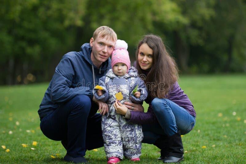 Gelukkige familie: Vader, Moeder en kind - meisje in de herfstpark: papa, mammababy openlucht stellen royalty-vrije stock fotografie
