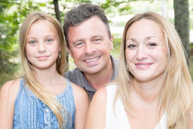 Gelukkige familie van drie die pret hebben samen openlucht stock fotografie