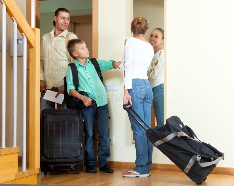 Gelukkige familie van drie met tiener die met bagage ho verlaten stock afbeeldingen