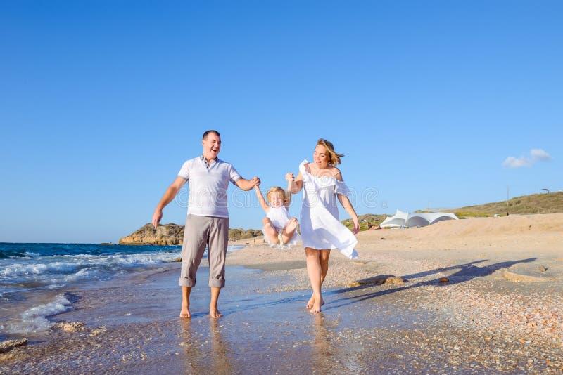 Gelukkige familie van drie - zwangere moeder, vader en dochterholdingshanden en het hebben van pret die op het strand lopen Famil stock fotografie