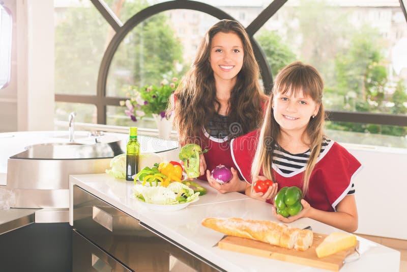 Gelukkige familie van het jonge meisjes koken Vegetarische maaltijd bij keuken royalty-vrije stock afbeeldingen