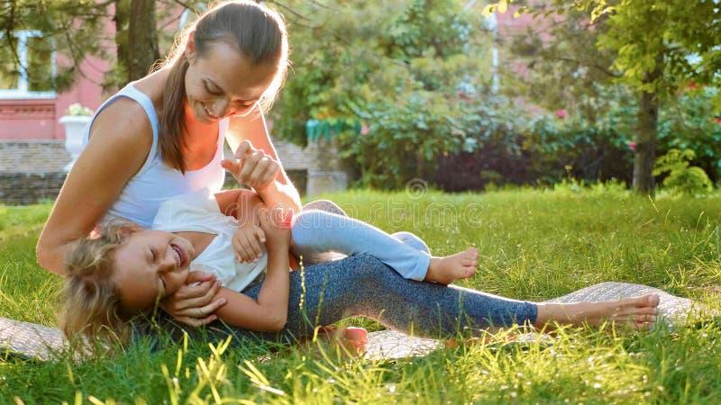 Gelukkige familie van jonge sportieve moeder en weinig leuke dochter die pret hebben in openlucht stock fotografie
