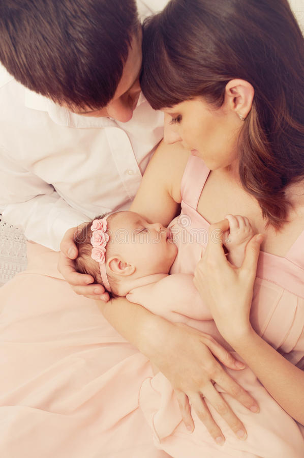 Gelukkige familie van twee die het leuke meisje van de slaap pasgeboren baby houden stock afbeelding