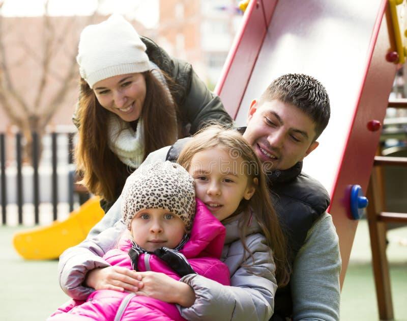 Gelukkige familie van vier bij de speelplaats van kinderen stock afbeeldingen