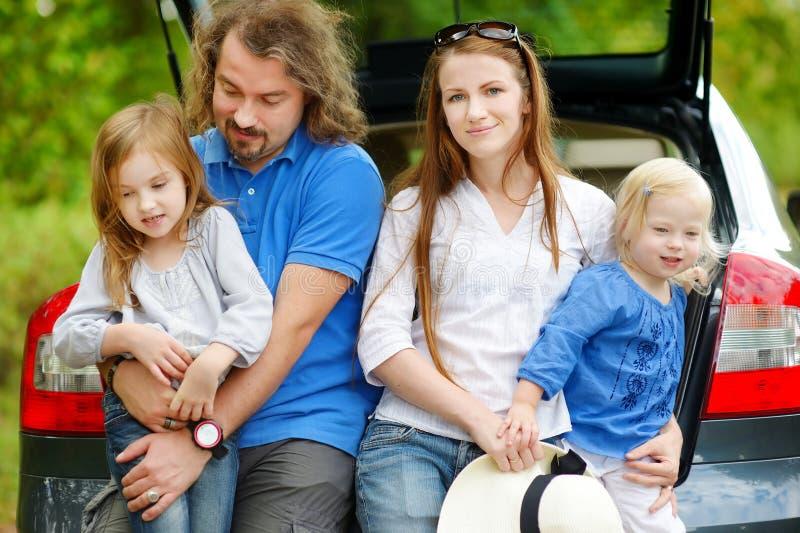 Gelukkige familie van vier die naar een autovakantie gaan royalty-vrije stock afbeeldingen